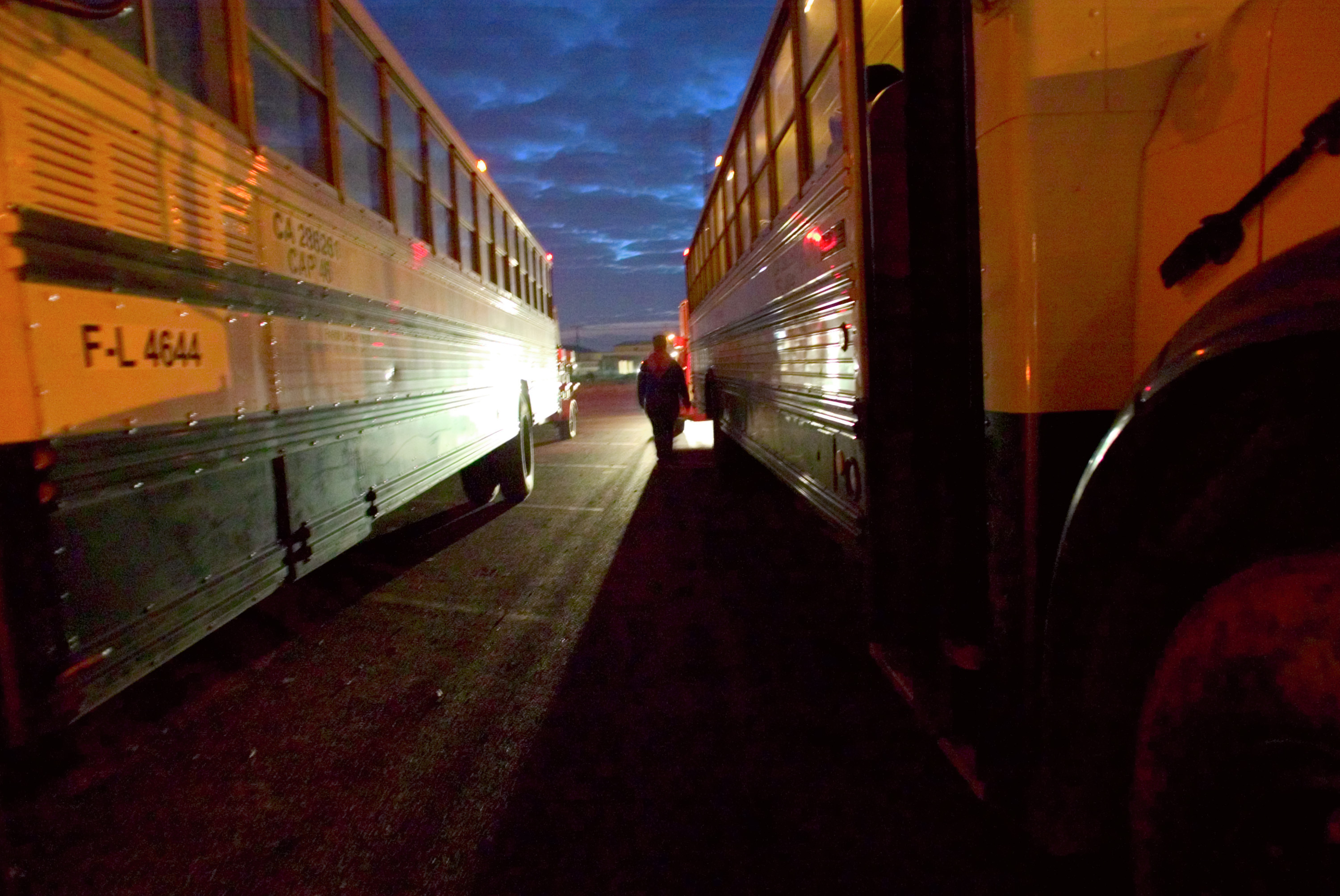 Farmworkers board buses in the early morning hours in Huron, California.
